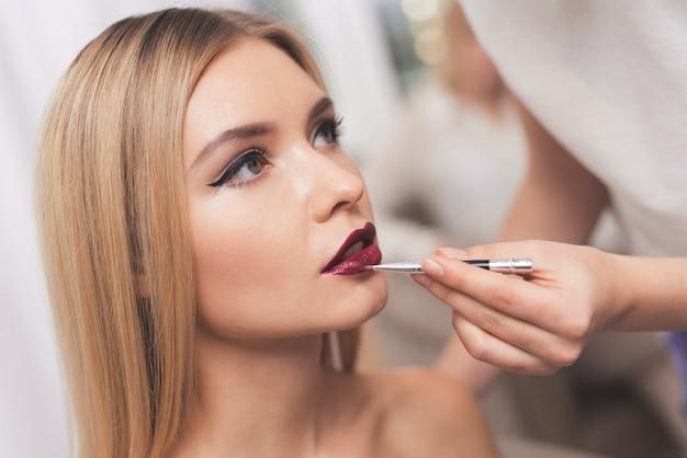 Uma menina loira é dada a maquiagem em um salão de beleza.