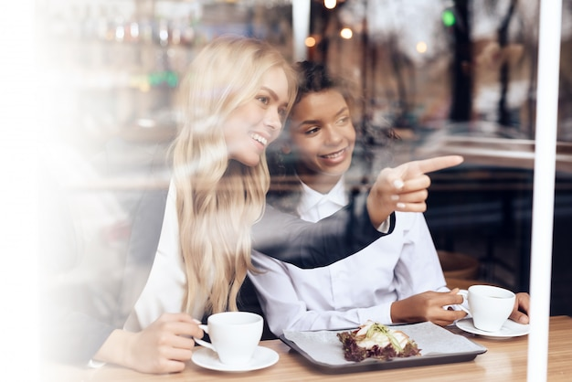 Uma menina loira e uma mulata estão sentadas em um café.