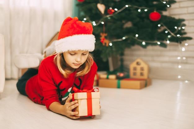 Uma menina loira está deitada no chão ao lado de uma árvore de natal decorada e segura um presente amarrado com