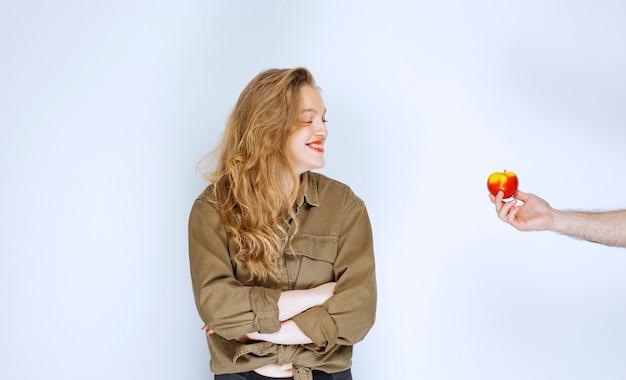 Uma menina loira está recebendo uma maçã vermelha ou pêssego, mas ela não aceita.