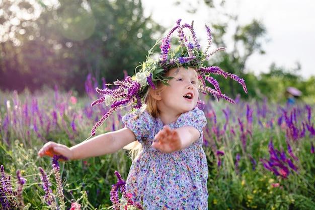 Uma menina loira feliz com uma coroa de sálvia e um vestido colorido em um campo florido de verão