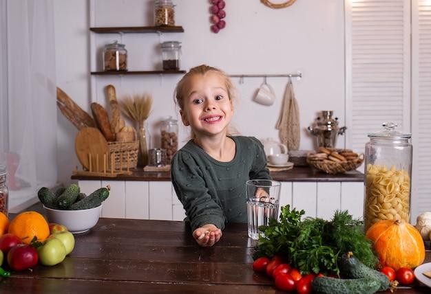 Uma menina loira feliz está sentada à mesa com um copo de água e vitaminas