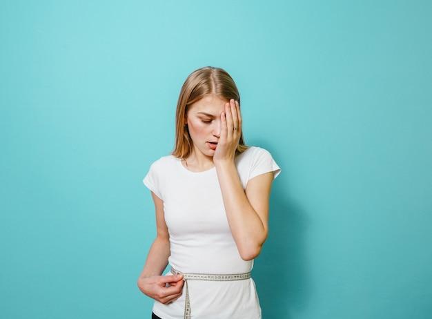Uma menina loira medindo a cintura com o medidor