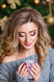 Uma menina luxuosa na roupa feita malha com composição e manicure brilhante prende um copo nas mãos de decorações de um natal. fechar-se
