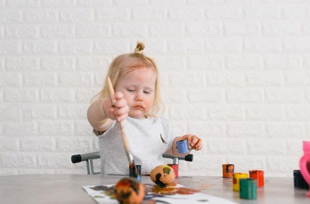 Uma menina manchada de tinta aprende a pintar ovos para o feriado da páscoa. em casa na cozinha