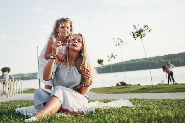 Uma menina maravilhosa faz bolhas com a mãe no parque.