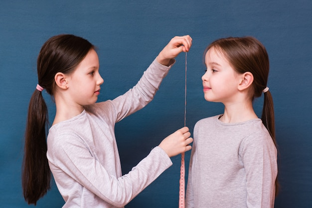 Uma menina mede outro crescimento com uma fita métrica em um fundo azul