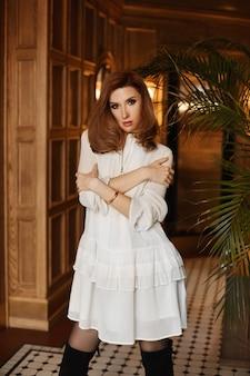 Uma menina modelo com corpo perfeito em um vestido de cocktail em pé com os braços cruzados no interior de luxo