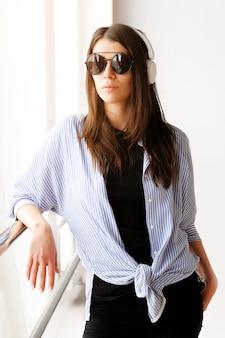Uma menina morena bonita e confiante em elegantes óculos e fones de ouvido escuta música no aeroporto ou no escritório. freelancer fêmea novo no t-shirt preto e na camisa leve. os óculos refletem a cidade