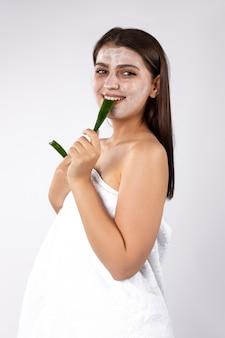 Uma menina morena com máscara facial no rosto mostra uma folha de aloés quebrada na foto dos dentes em um branco