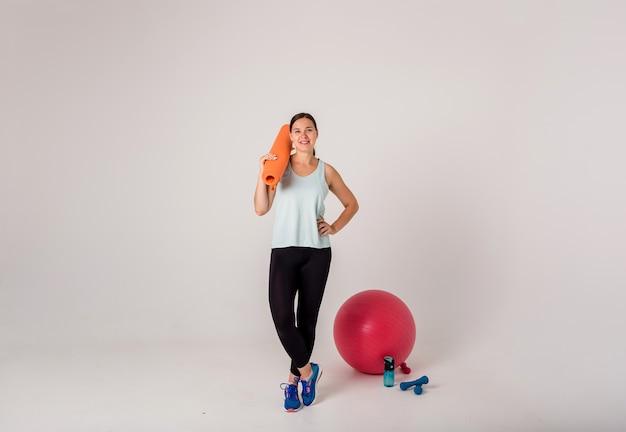 Uma menina morena com um tapete laranja e calção esporte em um branco em pleno crescimento