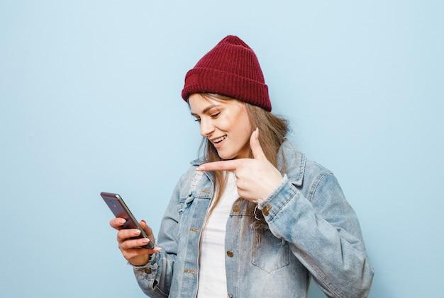 Uma menina morena com um telefone celular que se faz selfie e feliz sobre um fundo azul
