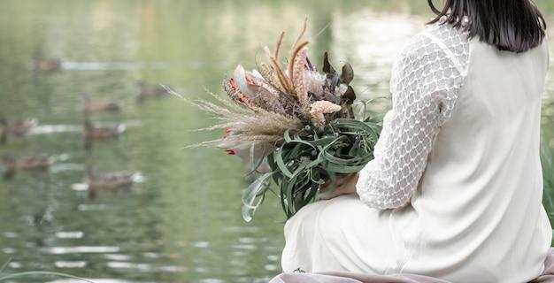 Uma menina morena com um vestido branco senta-se à beira do rio com um buquê de flores exóticas, fundo desfocado, vista traseira.