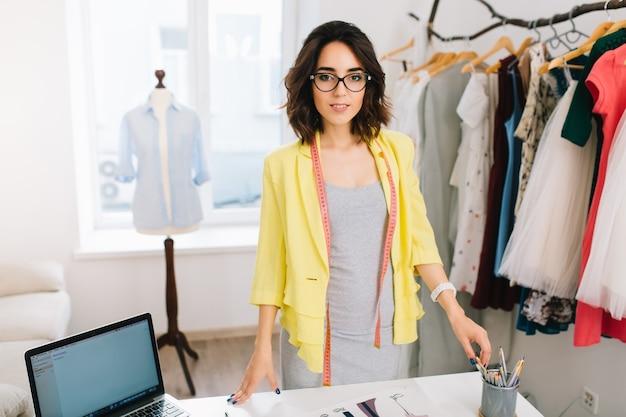 Uma menina morena com um vestido cinza e uma jaqueta amarela está de pé perto da mesa em um estúdio. ela tem muitas coisas criativas sobre a mesa. ela está sorrindo para a câmera.