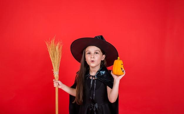 Uma menina morena com uma fantasia de bruxa com um chapéu segura uma vassoura e uma abóbora em um fundo vermelho com uma cópia do espaço