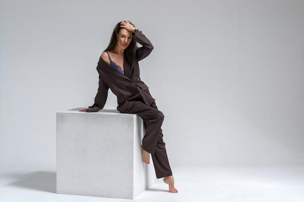 Uma menina morena em um terno marrom estrito está sentada sobre um cubo branco sobre um background.emotions branco de uma mulher de negócios.