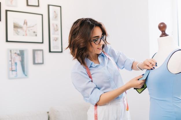 Uma menina morena está criando um vestido azul no estúdio. ela tem coisas de costura nas mãos, olhando seu trabalho. há muitas fotos de fundo.