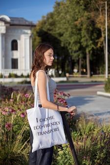 Uma menina morena está de pé ao lado de scooter elétrico no parque e tira de um saco de pão