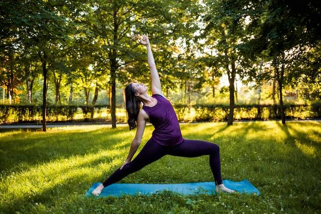 Uma menina morena executa utthita trikonasana yoga asana na natureza ao pôr do sol