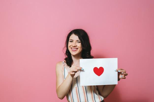 Uma menina morena feliz segurando um espaço em branco branco com um coração em uma parede rosa