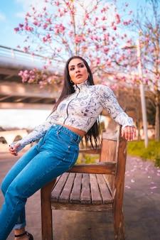 Uma menina morena latina sentada em um parque na cidade ao lado de uma árvore com flores cor de rosa