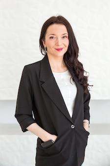 Uma menina morena linda e elegante em uma jaqueta preta mantém as mãos nos bolsos, sorri e olha para a câmera. garota posando contra uma parede branca.