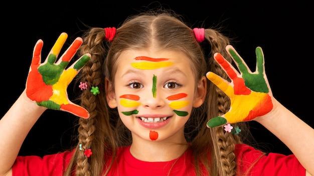 Uma menina mostra as mãos manchadas com tintas a guache.