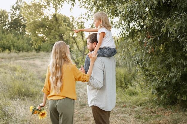 Uma menina mostra seus pais à esquerda em uma caminhada