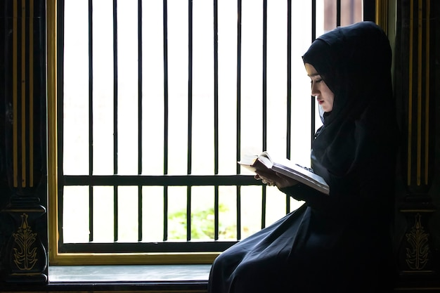 Uma menina muçulmana coloque lenço preto na cabeça estava lendo textos islâmicos. estritamente