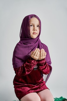 Uma menina muçulmana em um hijab reza