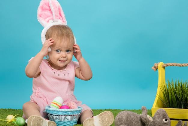 Uma menina na grama verde e fundo azul nas orelhas de um coelhinho da páscoa com ovos de páscoa pintados se preparando para a páscoa