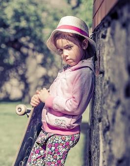 Uma menina na moda está segurando um skate e brincando lá fora, as emoções bonitas de uma criança.