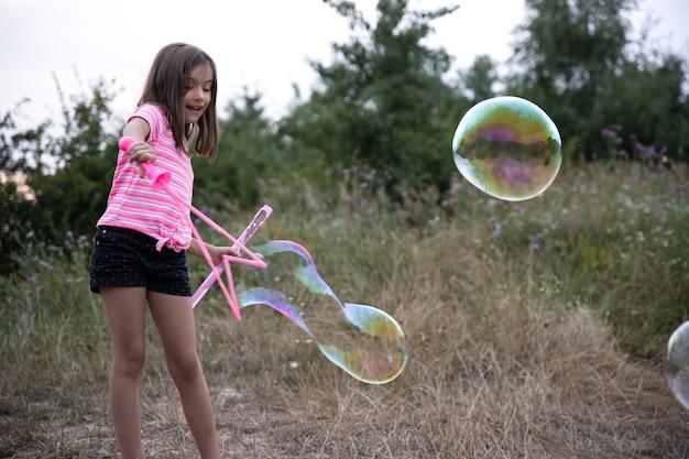 Uma menina na natureza brinca com grandes bolhas de sabão.