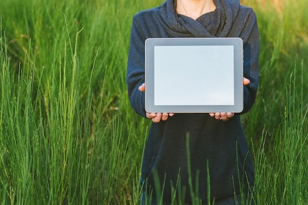 Uma menina na natureza tem um tablet nas mãos num contexto de uma bela vegetação.
