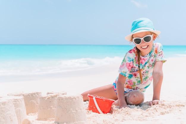 Uma menina na praia brinca com a areia e faz um castelo de areia