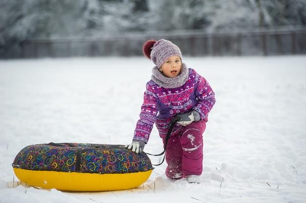 Uma menina no inverno com roupas roxas e um círculo inflável anda na rua em uma floresta coberta de neve.