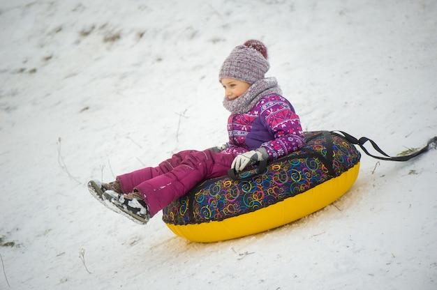 Uma menina no inverno com roupas roxas e um círculo inflável desce a colina na rua