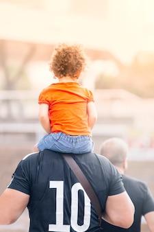 Uma menina nos ombros de seu pai, um homem forte com seu parceiro, caminha durante o pôr do sol