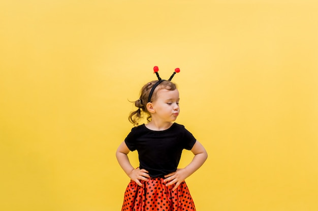 Uma menina ofendida em uma fantasia de joaninha em um amarelo isolado