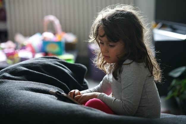 Uma menina olha e usa um telefone inteligente sentado em sua casa