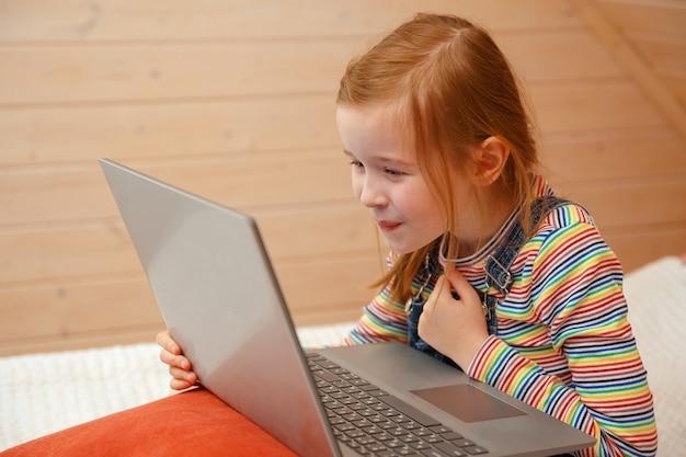Uma menina olha para o computador com emoções diferentes. menina brincando no computador