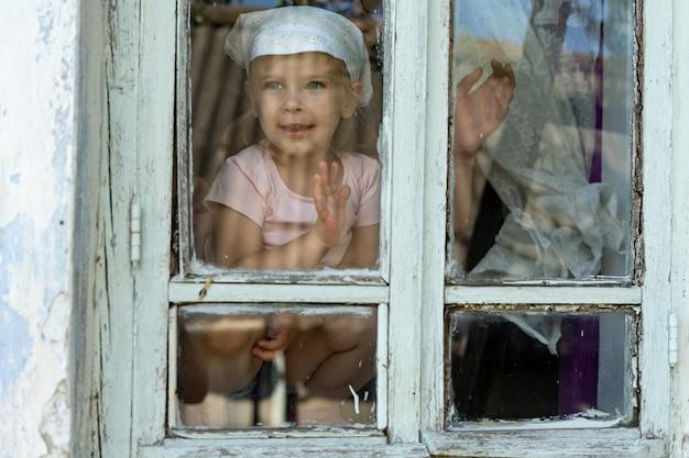 Uma menina olha pela janela de uma velha casa de aldeia