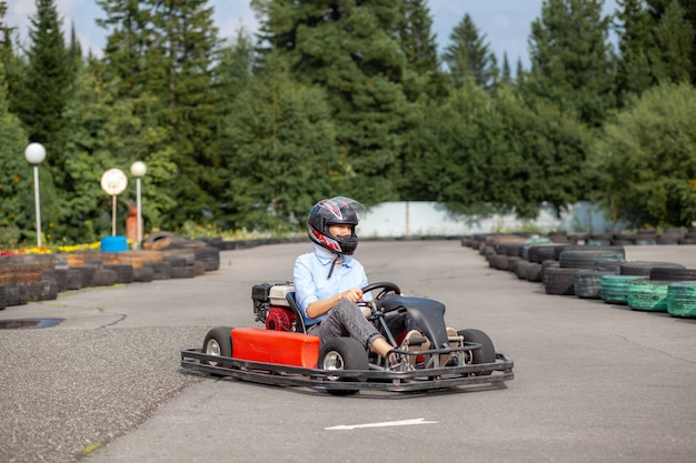 Uma menina ou mulher com capacete de proteção anda de kart em uma pista especial com rodas de borracha. recreação ativa e esportes no transporte. preparação e treinamento para competições.