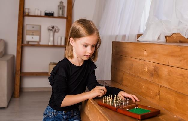 Uma menina pensativa está jogando xadrez em uma sala