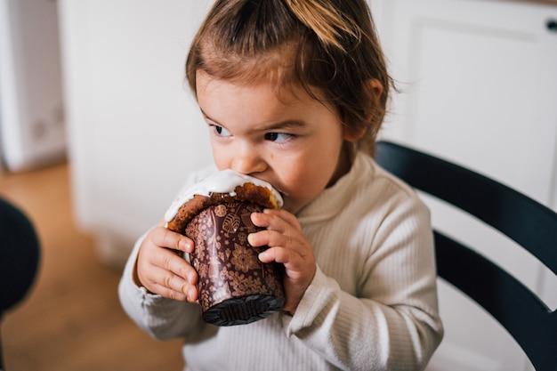 Uma menina pequena criança comendo bolo de páscoa para a páscoa ortodoxa