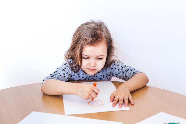 Uma menina pequena e fofa senta-se à mesa e desenha