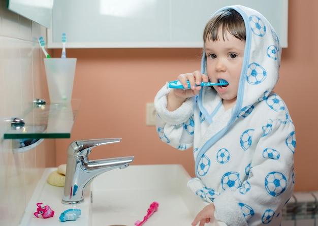 Uma menina pequena escova os dentes no banheiro. higiene da cavidade oral.