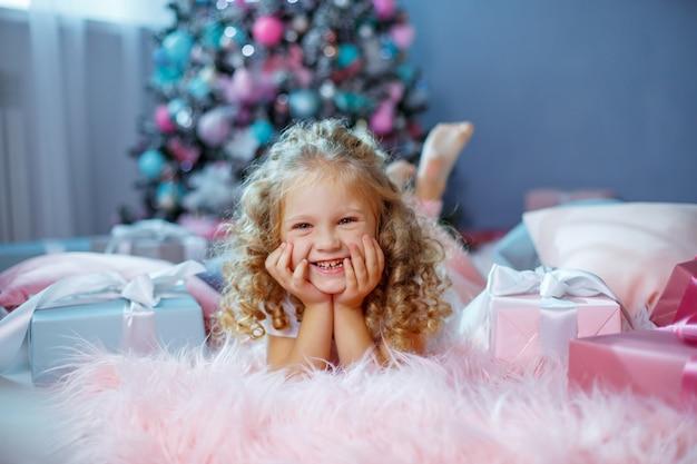 Uma menina perto da árvore de natal está deitada na cama