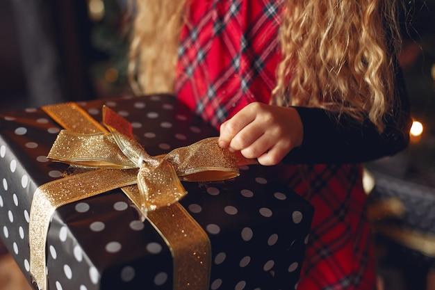 Uma menina perto de uma árvore de natal com um presente
