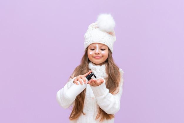 Uma menina pinga nas mãos um creme que protege a pele do frio do inverno.